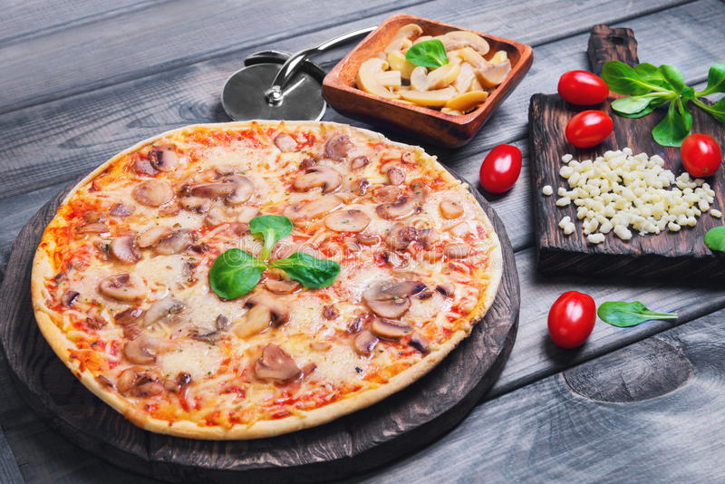 Pizza with mushrooms. A large pizza with mushrooms champignons, lettuce, cherry tomatoes, mozzarella cheese knife on wooden cutting board stands on a gray royalty free stock image