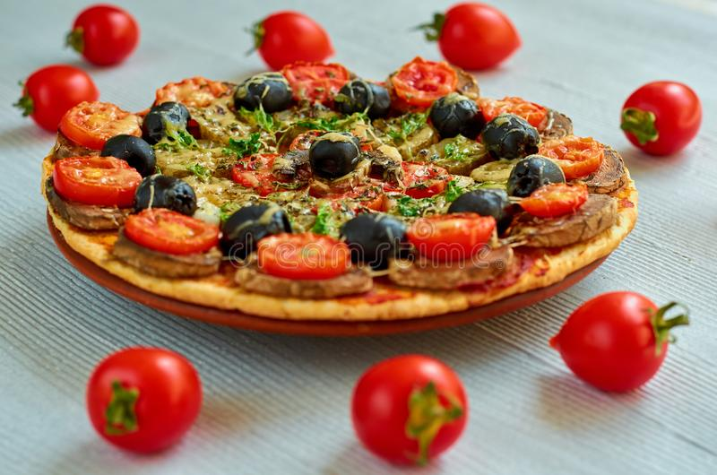Pizza with mushrooms, tomatoes, black olives and spices on the gray concrete background. Vegetarian pizza stock photos