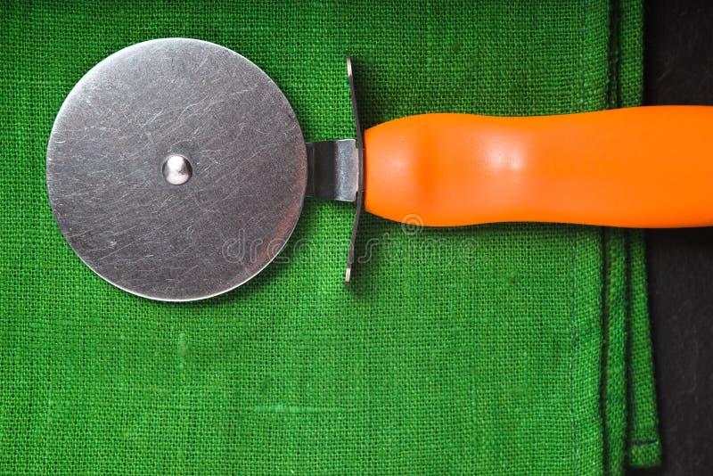 Pizza nóż na jaskrawym - zielona pielucha fotografia stock
