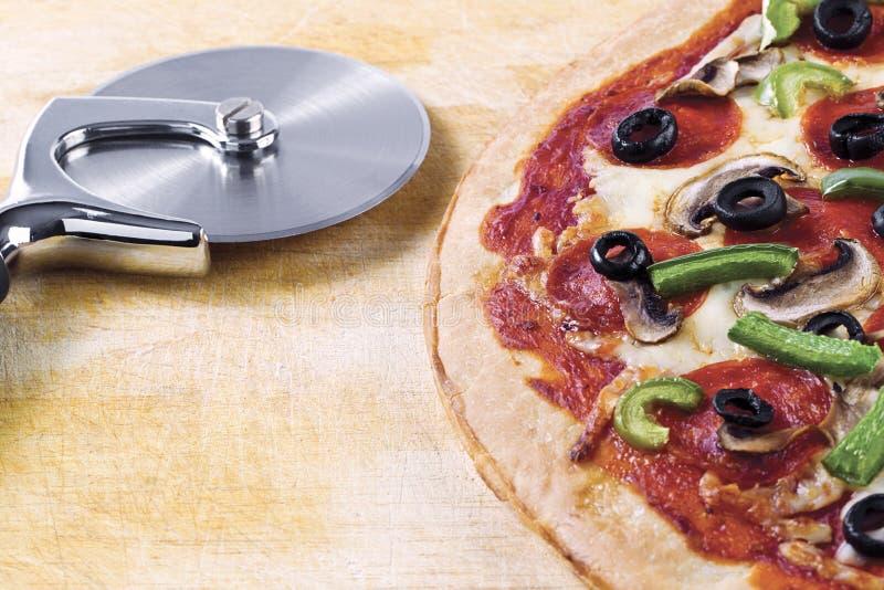Pizza och pizzaskärare royaltyfri fotografi