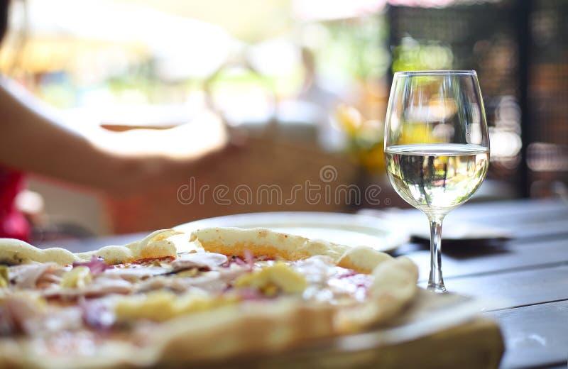 Pizza och vitt vin i utomhus- restaurang royaltyfri foto