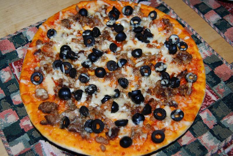 Pizza with olives and cheese on a napkin. royalty free stock photography