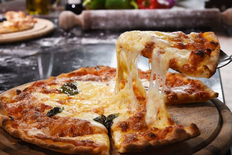 Pizza opheffende plak op houten raad stock afbeeldingen