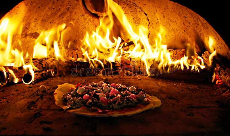 Pizza oven in flames stock photography
