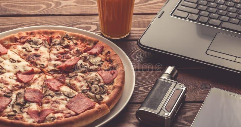 Pizza på en platta, en svart bärbar dator, en elektronisk cigarett eller vape, en mobiltelefon och ett exponeringsglas av fruktfr royaltyfri fotografi