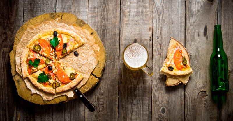 Pizza på träcirkel, öl och en flaska på en trätabell royaltyfri fotografi