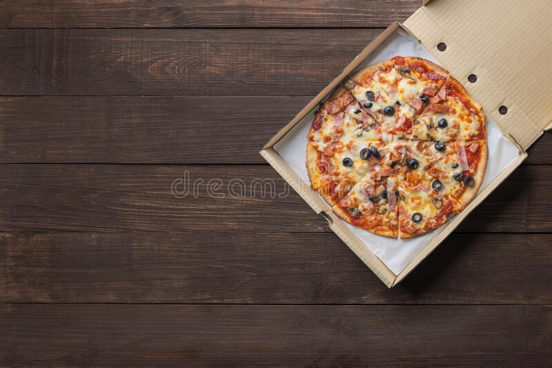 Pizza in paper box on wooden background. Copyspace for text and logo. Top view. Pizza in paper box on wooden background. Copyspace for text and logo. Top view stock images