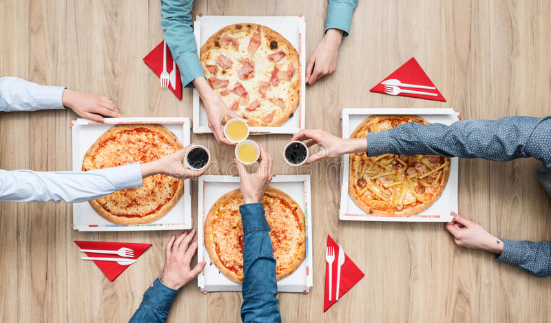 Pizza party. Group of friends having a pizza party at home and enjoying together, they are toasting with drinks, flat lay stock photos