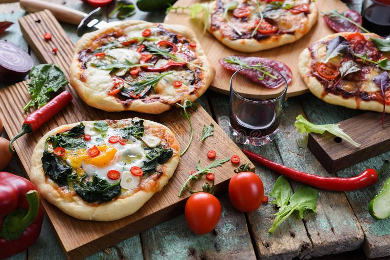 Pizza party. Small homemade rustic pizzas with eggs, spinach, sa royalty free stock images