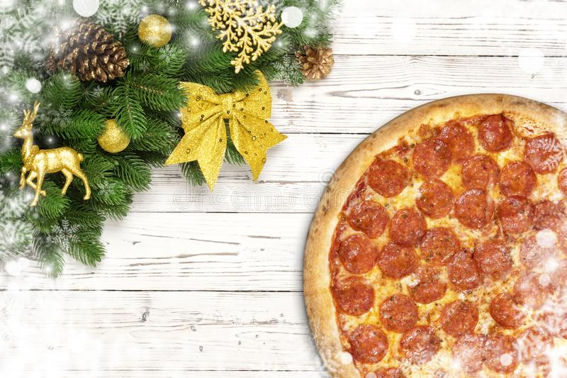 Pizza pepperoni Christmas snowflake with fir branches and new year toy ball, deer or reindeer, bow on white wood board.  stock images