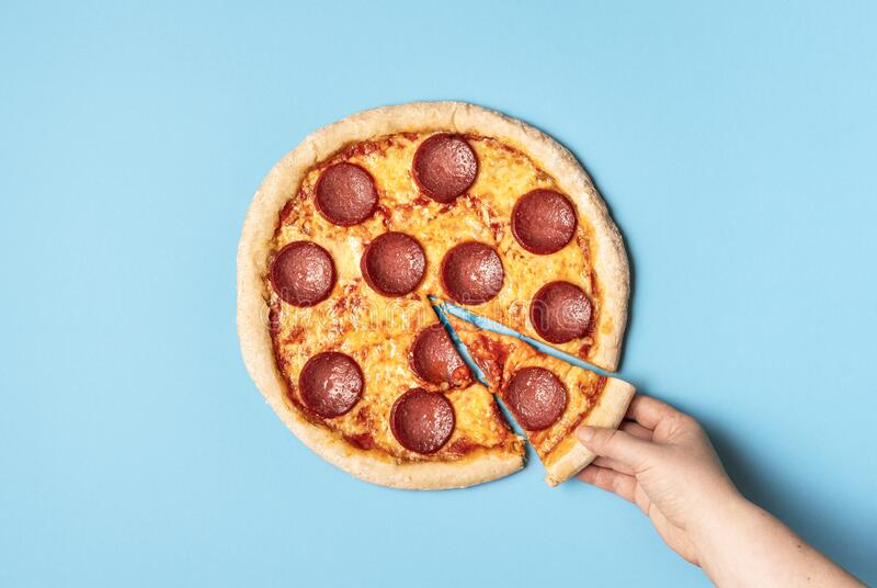 Pizza pepperoni and taking a slice of pizza. Eating pizza salami. Woman taking one slice of pizza salami on a blue background. Above view of pepperoni pizza and stock images
