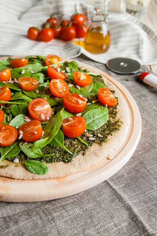 Pizza with pesto, spinach and cherry tomatoes royalty free stock photos