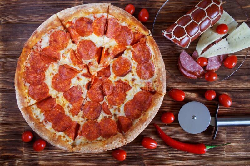 Pizza picante caseiro com pepperoni e mentiras em uma superfície de madeira ao lado de uma faca circular especial, tomates do sal fotografia de stock royalty free