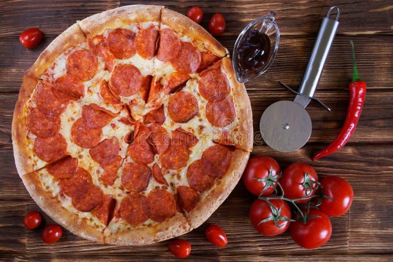 Pizza picante com mentiras do salame e dos pepperoni em uma superfície de madeira ao lado de uma faca circular especial, de uns t imagem de stock royalty free