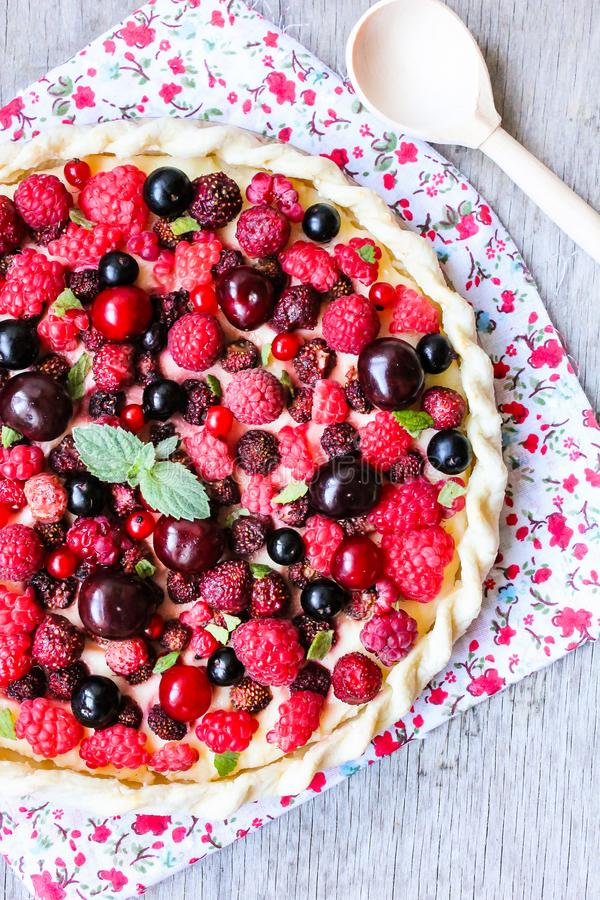 Pizza pie with mascarpone cream cheese, raspberry, black currant, strawberry, cherry on a wooden table. Homemade pie. Fruit pizza. royalty free stock image