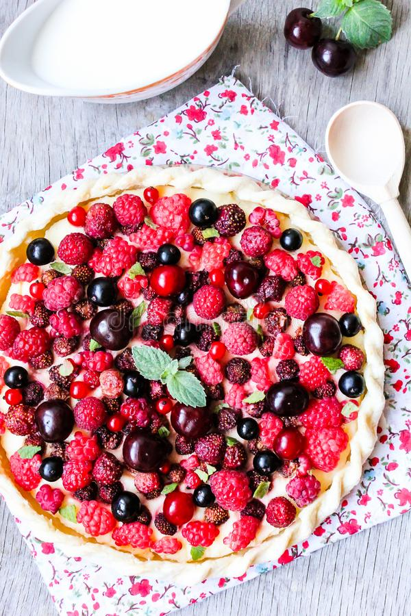 Pizza pie with mascarpone cream cheese, raspberry, black currant, strawberry, cherry on a wooden table. Homemade pie. Fruit pizza. stock photo