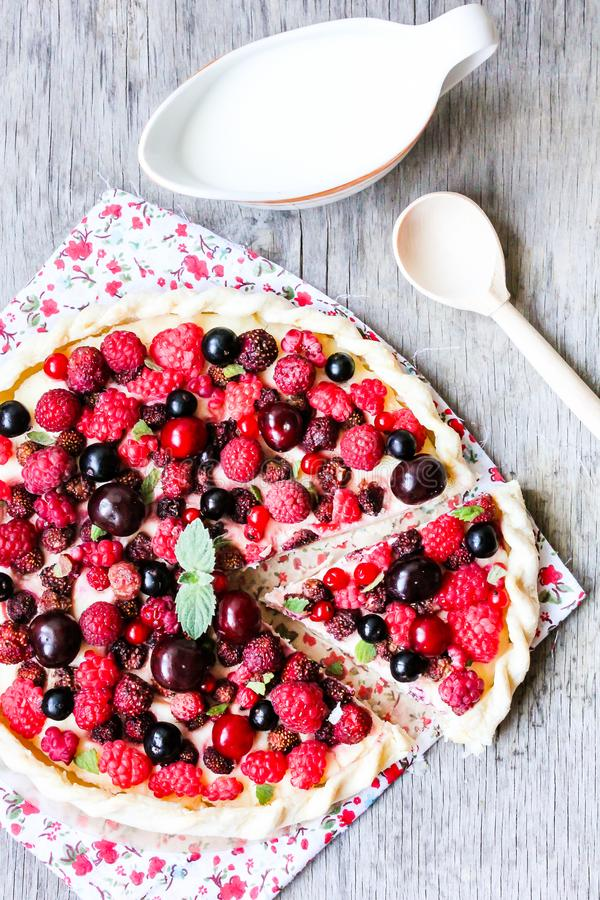 Pizza pie with mascarpone cream cheese, raspberry, black currant, strawberry, cherry on a wooden table. Homemade pie. Fruit pizza. royalty free stock photos