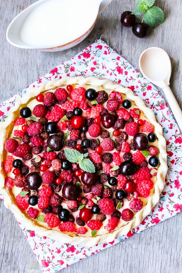 Pizza pie with mascarpone cream cheese, raspberry, black currant, strawberry, cherry on a wooden table. Homemade pie. Fruit pizza. stock images