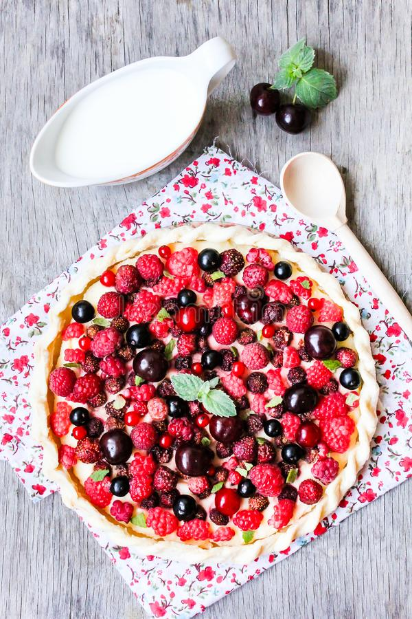 Pizza pie with mascarpone cream cheese, raspberry, black currant, strawberry, cherry on a wooden table. Homemade pie. Fruit pizza. stock photos
