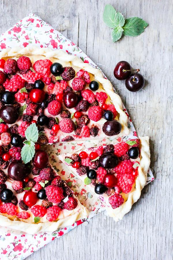 Pizza pie with mascarpone cream cheese, raspberry, black currant, strawberry, cherry on a wooden table. Homemade pie. Fruit pizza. stock image