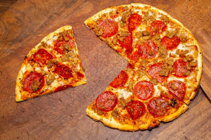 Pizza pie with a quarter removed to demonstrate math fractions. stock images