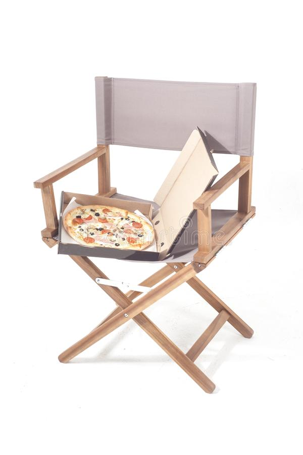 Pizza in pizza box on director chair. Isolated on white background royalty free stock photo