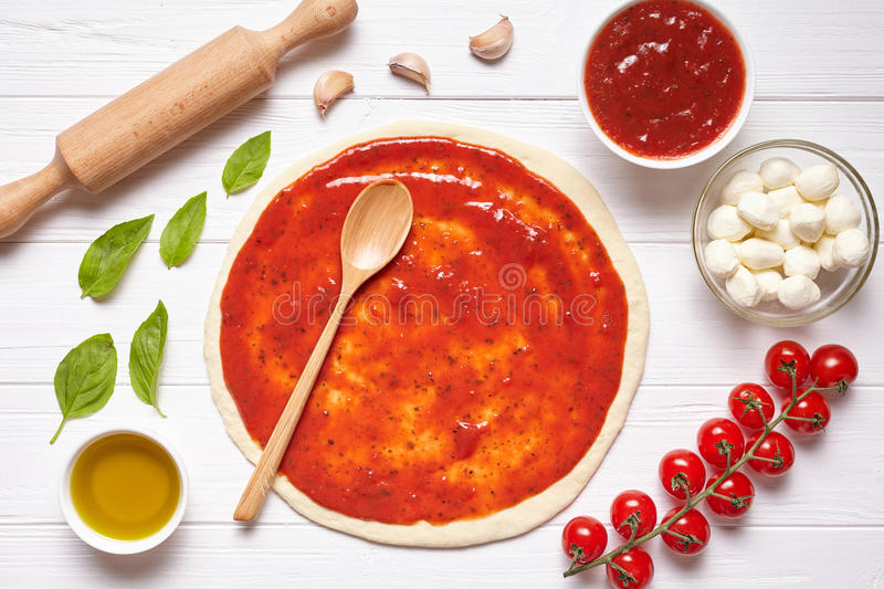 Pizza preparation. Baking ingredients on the kitchen table: rolled dough with tomatoes sauce stock image