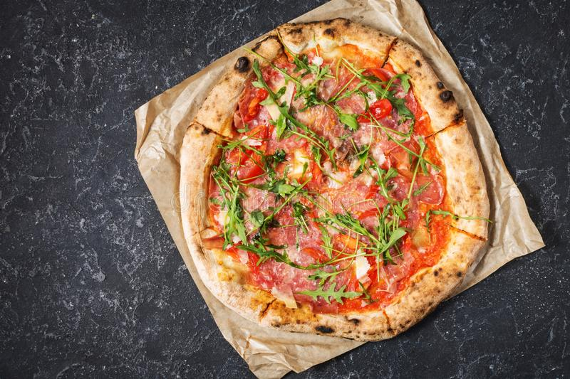 Pizza with prosciutto, arugula and parmesan on black stone background. Top view. royalty free stock photo