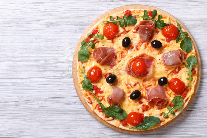 Pizza with prosciutto and arugula top view horizontal royalty free stock photography