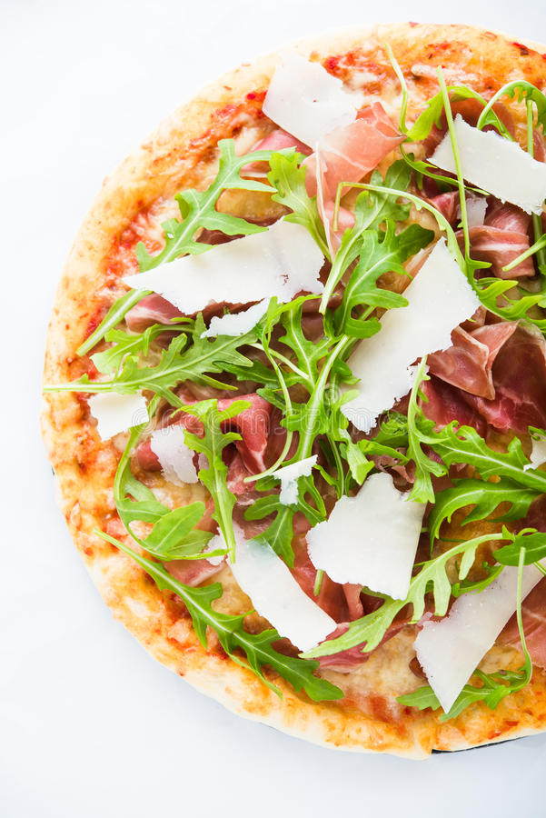 Pizza with prosciutto parma ham, arugula (salad rocket) and parmesan top view royalty free stock photography