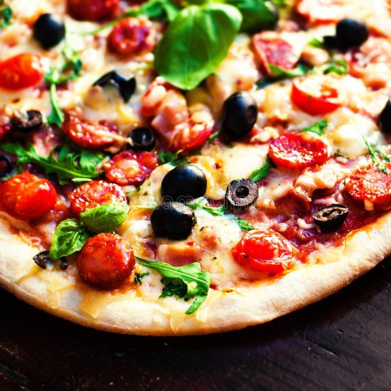 Pizza quente com queijo da carne, da manjericão e do mozarella em um backgr escuro fotos de stock