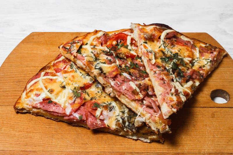 Pizza rústica italiana, tres pedazos en una bandeja de madera, tabla de madera blanca, con los tomates y el queso fotos de archivo