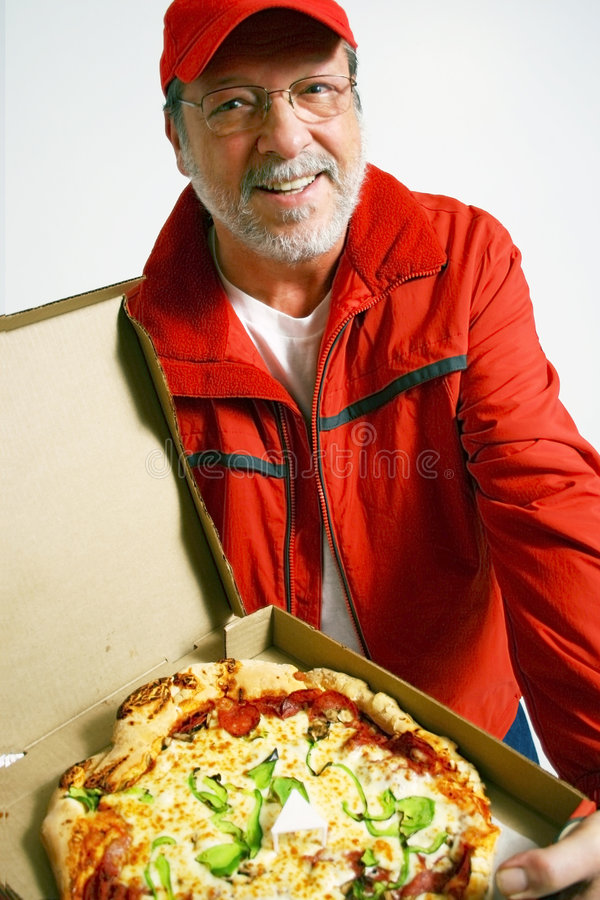 Pizza is ready. Senior man with red uniform and smile delivered an all dressed pizza royalty free stock photography