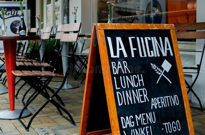 Pizza restaurant `La fucina`, Javastraat street, Amsterdam, Netherlands. View of advertising board against outside tables and chai royalty free stock photo