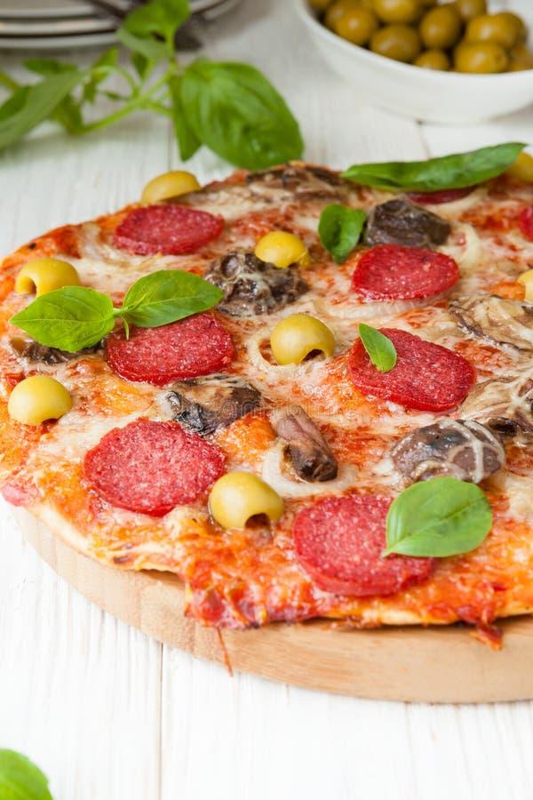 Pizza saboroso com fatias de salame nas placas brancas imagens de stock royalty free