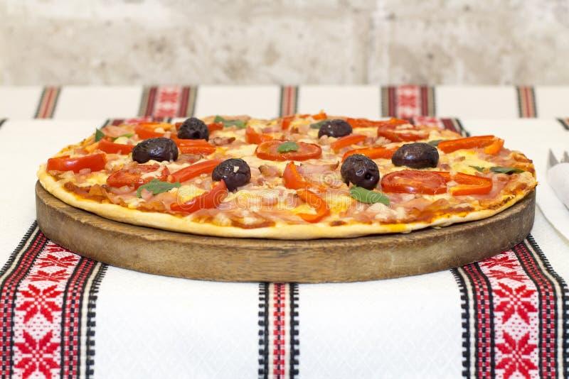 Pizza saboroso com vegetais, manjericão, azeitonas, tomates, pimenta verde na placa de corte, colorido tradicional de pano de tab foto de stock royalty free