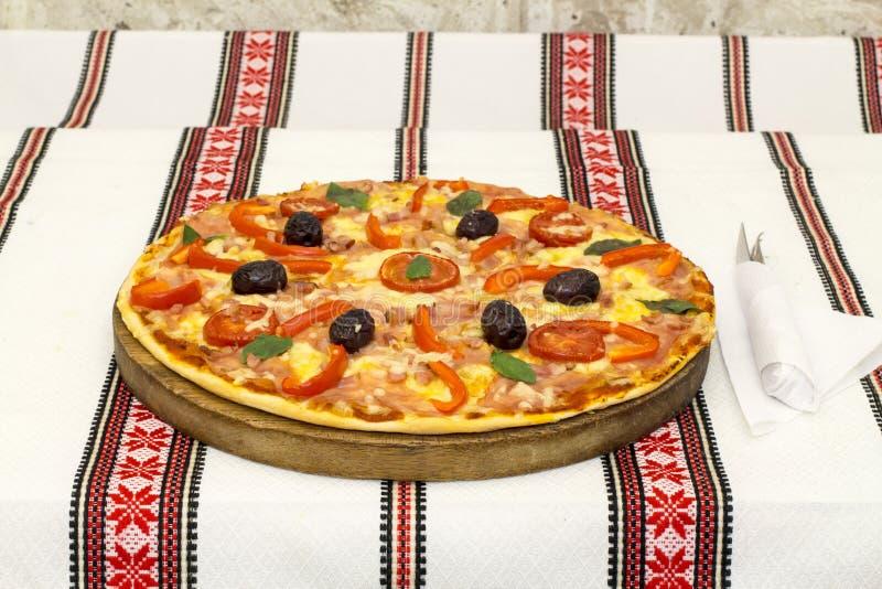 Pizza saboroso com vegetais, manjericão, azeitonas, tomates, pimenta verde na placa de corte, colorido tradicional de pano de tab fotos de stock royalty free