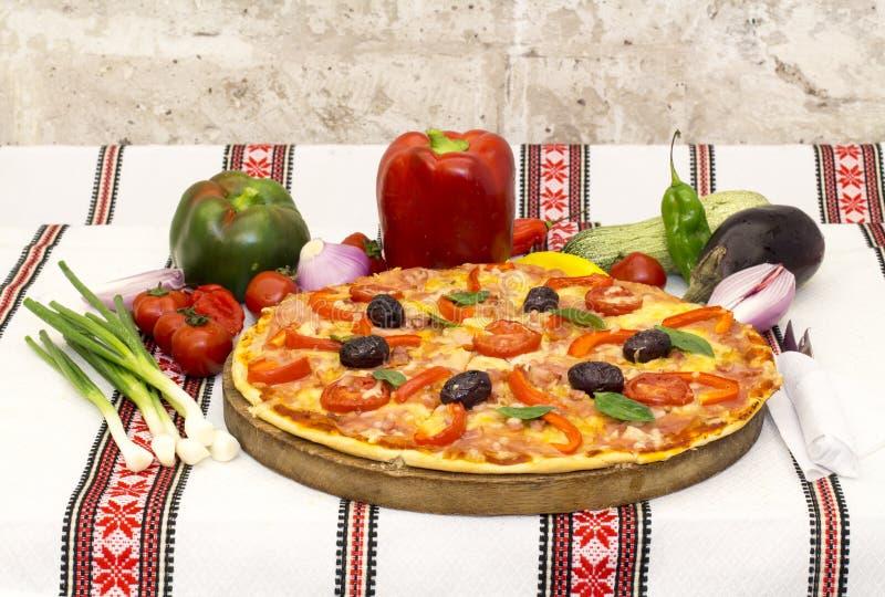 Pizza saboroso com vegetais, manjericão, azeitonas, tomates, pimenta verde na placa de corte, colorido tradicional de pano de tab fotografia de stock royalty free