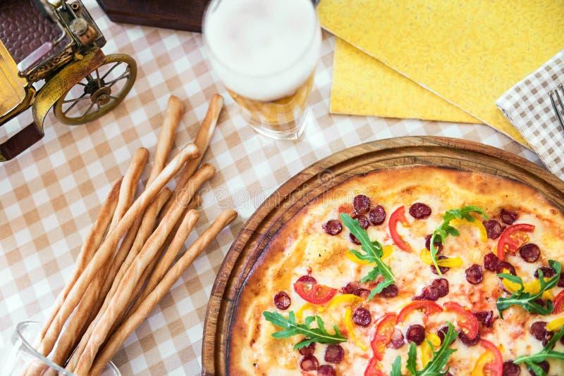 Pizza saboroso com vidro da cerveja, na tabela servida foto de stock royalty free