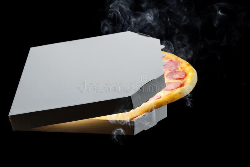 Pizza saboroso dos pepperoni quentes na caixa de cartão aberta, fumo de derretimento do vapor do queijo no fundo preto fotografia de stock royalty free