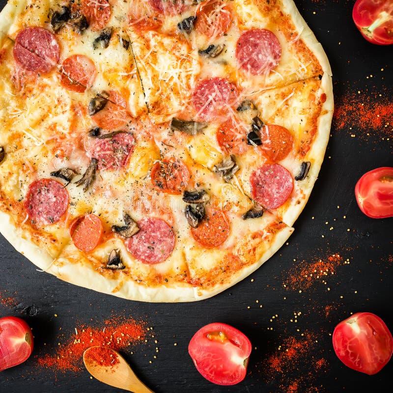 Pizza sabrosa con los ingredientes y las especias en fondo negro Endecha plana, visión superior imagen de archivo