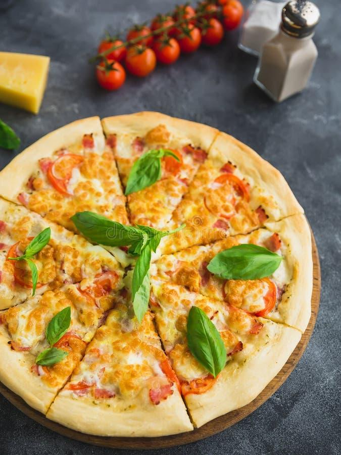 Pizza sabrosa con tocino, queso y el tomate en fondo oscuro Opinión del primer Alimento delicioso foto de archivo