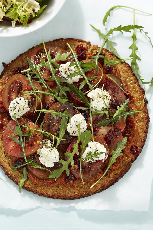 Pizza saine de quinoa avec des tomates et des tomates et le fromage de chèvres séchés au soleil photo libre de droits
