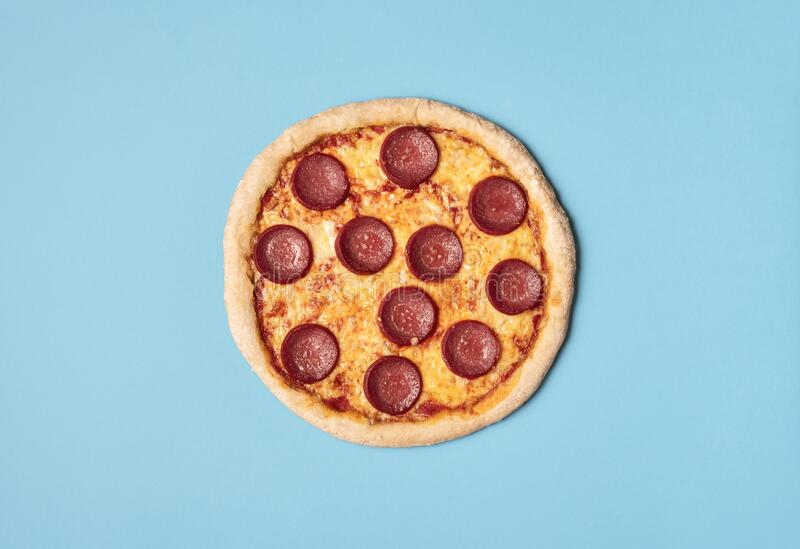 Pizza salami on a blue background. Whole pizza pepperoni. Food. Tasty pizza salami with melted cheese, mozzarella and tomato sauce on a blue background. Above stock photos