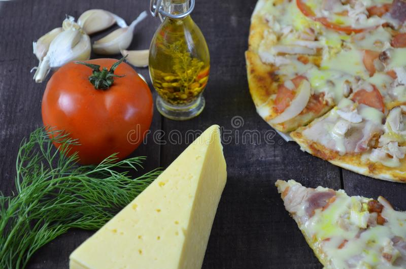 Pizza salami cheese ham. Hot Homemade Pepperoni Pizza Ready to Eat . with ingredients for cooking, greens, garlic, tomato, cheese. Pizza salami cheese ham. Hot royalty free stock photography
