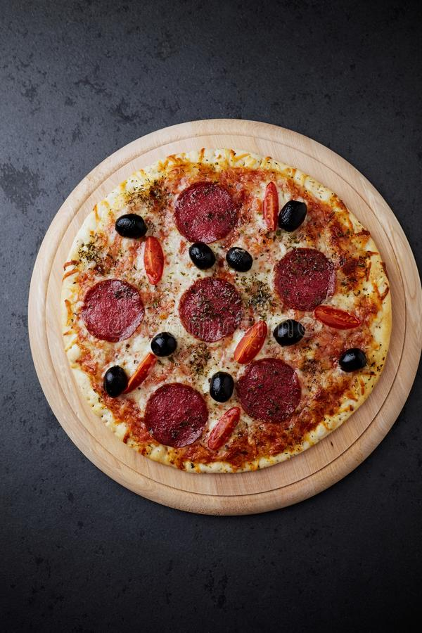 Pizza with salami, mozzarella cheese, cherry tomatoes, black olives and oregano. Home made food. Concept for a tasty and hearty me royalty free stock photos