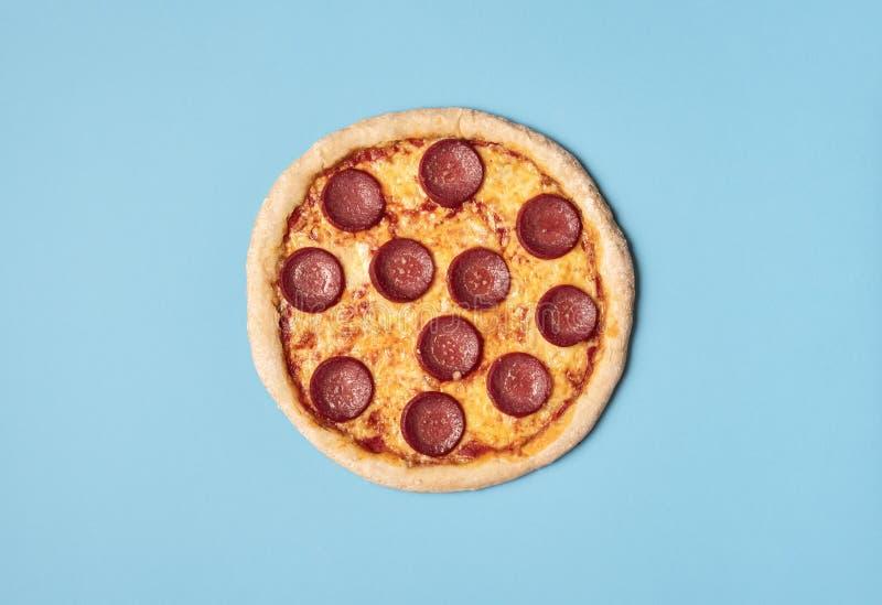 Pizza salami på blå botten Hel pizza pepperoni Livsmedel arkivfoton