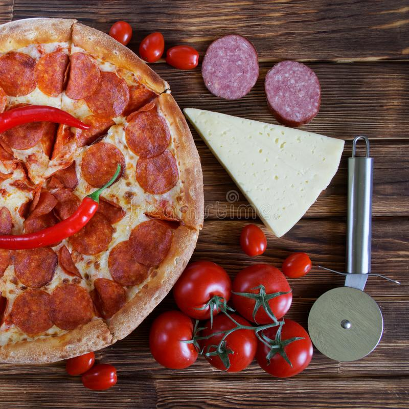 Pizza with salami and red chili lies on a wooden table next to a special circular knife, sliced sausage, a piece of cheese and a royalty free stock image