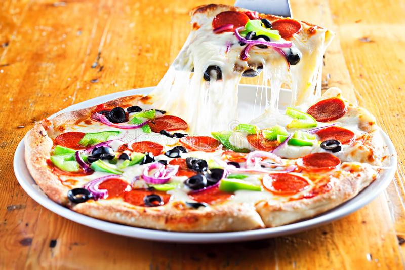 Pizza with salami, red onion, peppers and black olives stock photography