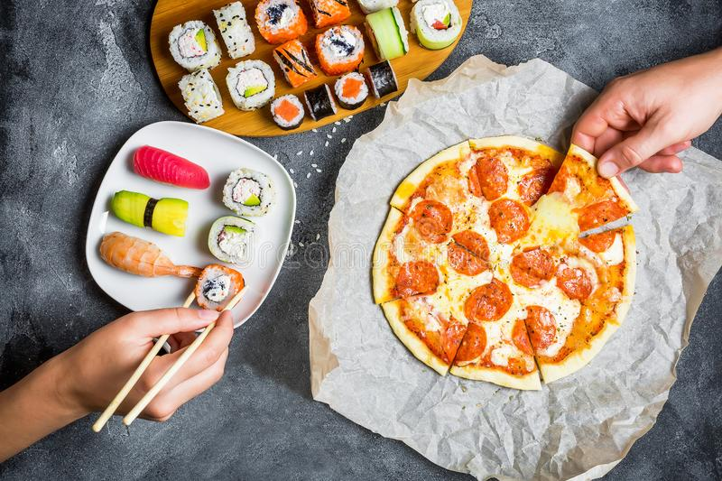 Pizza with salami, set of sushi rolls and hands take food. Food background. Flat lay, top view. royalty free stock photos